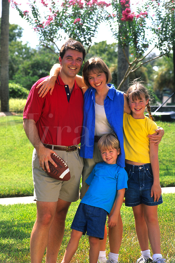 Young affluent family spending quality time together while playing football at a local park