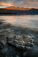 Golden nuggets like rocks on shores of Lake Wakatipu at sunset, Remarkables Mountains in background, Oueenstown, Central Otago, New Zealand, NZ