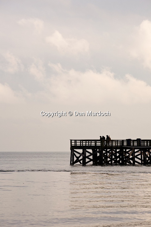 Fishing pier with people on flat water and under cloudy skies.