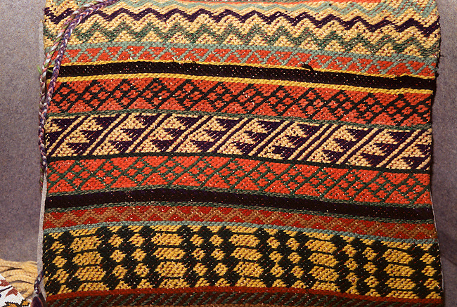 Miami tribe traditionally finger woven fabric made from colorful yarn and made into a pillow cover.