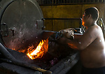 21 May 2019, Klagen Tropodo, East Java, Indonesia A local man feeds plastic fuel in to a furnace at a factory producing tofu at Klagen Tropodo village outside Surabaya, Indonesia. Millions of tonnes of recyclable plastic trash from Australia and Europe is dumped for rag pickers to separate and sort. The plastics are used to fuel fires at local tofu factories among other industries. Australia is illegally sending non recyclable trash hidden within this lode and the Indonesian Government is cracking down on the practice and preparing to refuse to take Australia's rubbish that is creating environmental and health issues locally. Picture by Graham Crouch/The Australian