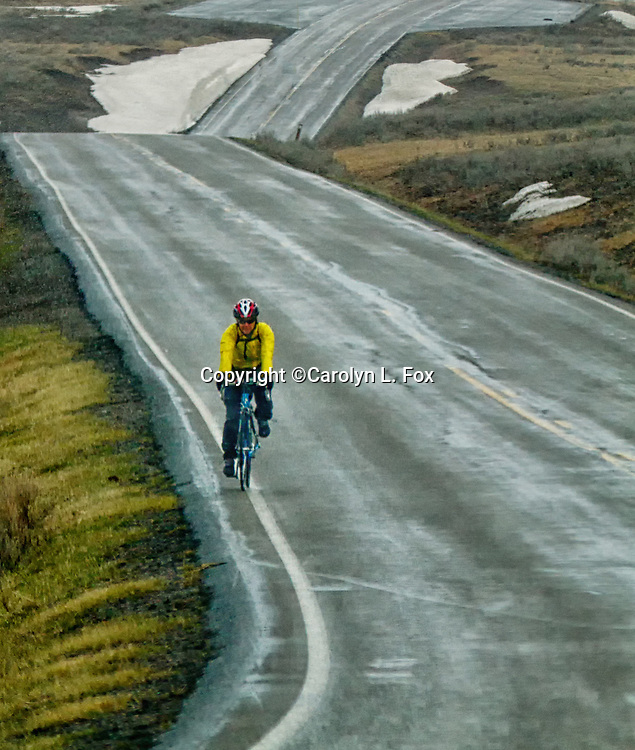 A man rides a bicycle down a wet road in Idaho.