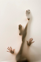 Partially silhouetted nude woman's hands and legs behind translucent fabric.