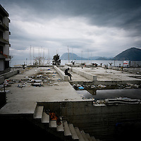 An Afghan refugee sits alone on the roof of one building squatted by hundreds of other Afghans that come to Europe to find a better life. Some of them have been walking for months to reach Greece to end up in a Patras shantytown where they will wait for months to go somewhere else in Europe. Patras is home to about 3,000 illegal immigrants. Most of them are Afghans, although there are also some Iranians and Uzbeks. They stop in Patras to try and find passage to various European destinations by hiding in ships, containers and trucks parked in the port. If they are lucky they will make it to their destination. Many of them live in shacks made from cartons, plastic and wood they found on the beach. To shelter from the cold they also squat in abandoned buildings, living without water and electricity. The living conditions are inhumane and unhygienic.