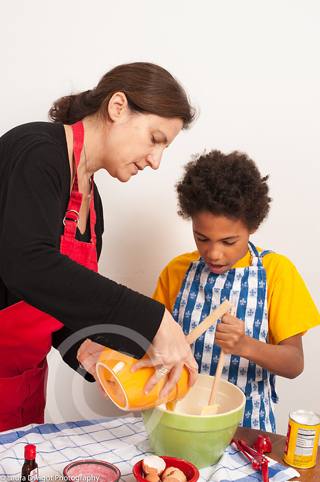 8 year old boy at home with mother at home in kitchen learning to bake, stirring as she adds ingredients