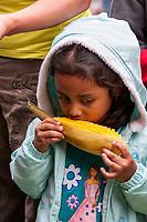 Antigua, Guatemala.  Little Girl Eating Roasted Corn on the Cob, Plaza de Armas.  Semana Santa.