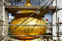 Switzerland. Geneva.The Russian Church (full name: Cathédrale de l'Exaltation de la Sainte Croix) is designed in a Byzantine Moscovite style. The church is a lovely 19th-century Russian Orthodox church topped with golden onion domes. The roof and all onion domes undergo a complete revival restoration by the roofing company « Cerutti Toitures SA ». A worker with a red hard hat from the Implenia company stands close to the old central golden bulb which will soon be dismantled. An onion dome is a dome whose shape resembles an onion. Such domes are often larger in diameter than the drum upon which they sit, and their height usually exceeds their width. These bulbous structures taper smoothly to a point. The Russian church serves today not only the Russian community but also Bulgarians, Serbs, Coptic Christians and other Orthodox worshippers who do not have their own church in Geneva. Implenia is the largest construction company in Switzerland. 25.04.2016 © 2016 Didier Ruef