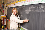 K-8 Parochial School Bronx New York Grade 3 female teacher working on blackboard mathematics lesson on measurement horizontal