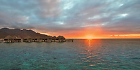 Sunset rays on overwater bungalows and the mountains of Moorea island, a honeymoon destination near Tahiti, French Polynesia, Pacific Ocean