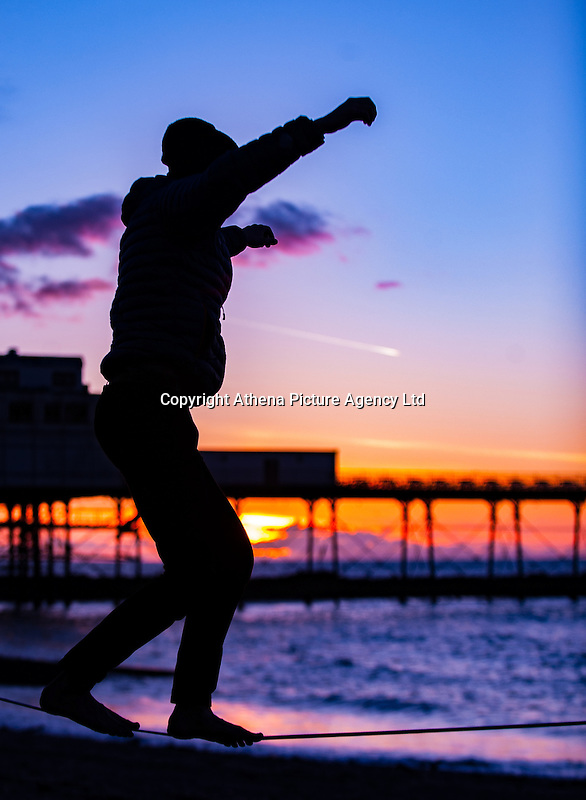 Aberystwyth, UK 23rd February 2016 A man balances himself on a wire on the beach, while the sun is setting by Aberystwyth pier in west Wales.