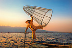 """A fisherman balances precariously on the edge of his boat on Inle Lake, Myanmar, demonstrating a technique dating back to the 12th century.<br /> <br /> The image was captured by photographer Istvan Kadar who said, """"This lake in Myanmar is famous for rowers masterfully balancing on one leg.  Photos of such hardworking fishermen are plentiful, but most are staged.  Of course, there are many """"real"""" fishermen plying Inle Lake with traps in order to bring home the catch to their families.""""<br /> <br /> """"The 'model' guys have figured out another way to make a few dollars off the lake—posing for tourists for tips.  They wear traditional, colourful clothing and perform amazing acrobatic shows; their sense of balance and the strength required to pose is quite remarkable.""""<br /> <br /> Please byline: Istvan Kadar/Solent News<br /> <br /> © Istvan Kadar/Solent News & Photo Agency<br /> UK +44 (0) 2380 458800"""