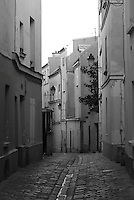Rue Saint Rustique, Montmartre, Paris, France.  One of the older streets at the top of this hill in Paris.  Leads to the place du Tertre, Saint Pierre and the Sacre Coeur.  Cobblestone paving maintains the historic feel of this village street.  historic appartments and homes reminicent of early Parisian Architecture.