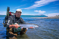 Sport fisherman holds a red salmon caught in the Brooks River in Katmai National Park, Alaska.