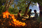 Women with children around a fire at Bagaman Island in the  Louisiade Archipelago..The Louisiade Archipelago is a string of ten larger volcanic islands frequently fringed by coral reefs, and 90 smaller coral islands located 200 km southeast of New Guinea, stretching over more than 160 km and spread over an ocean area of 26,000 km  between the Solomon Sea to the north and the Coral Sea to the south. The aggregate land area of the islands is about 1,790 kmu178  (690 square miles), with Vanatinai (formerly Sudest or Tagula as named by European claimants on Western maps) being the largest..Sideia Island and Basilaki Island lie closest to New Guinea, while Misima, Vanatinai, and Rossel islands lie further east..The archipelago is divided into the Local Level Government (LLG) areas Louisiade Rural (western part, with Misima), and Yaleyamba (western part, with Rossell and Tagula islands. The LLG areas are part of Samarai-Murua District district of Milne Bay. The seat of the Louisiade Rural LLG is Bwagaoia on Misima Island, the population center of the archipelago. .The Louisiade Archipalego is part of the Milne Bay province of Papua New Guinea..It lies between approximately 10 degrees south and 11.5 degrees south, and 151 degrees east and 154 degrees east. It is an area of Islands, reefs and cays some 200 nm long and 50 nm wide, stretching from the south east tip of mainland Papua New Guinea in a east south east direction..
