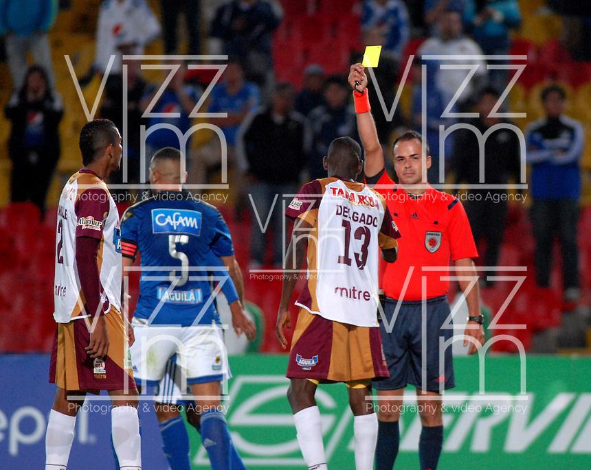 BOGOTA - COLOMBIA -28 -05-2015: Gustavo Gonzalez (Der), arbitro, muestra tarjeta amarilla a Didier Delgado (2 Der.), jugador de Deportes Tolima,durante partido aplazado entre Millonarios y Deportes Tolima, por la fecha 6 de la Liga Aguila II-2015, jugado en el estadio Nemesio Camacho El Campin de la ciudad de Bogota. / Gustavo Gonzalez (R), referee, shows yellow card to Didier Delgado (2R) player of Deportes Tolima, during a posponed match between Millonarios and Deportes Tolima, for the date 6 of the Liga Aguila II-2015 at the Nemesio Camacho El Campin Stadium in Bogota city. Photo: VizzorImage / Luis Ramirez / Staff.