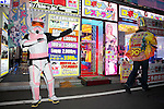 """July 23 2012, Tokyo, Japan - A man wears as a soldier of the Star Wars movie announces the """"Robot Restaurant"""" at Kabukicho in Shinjuku. The restaurant advertises that cost 10 billion yen (130 million) opening. Robots run by real women dressed in military, perform cabaret dance for its customers, opened in the Kabukicho area, Shinjuku in Tokyo. (Photo by Rodrigo Reyes Marin/AFLO)"""