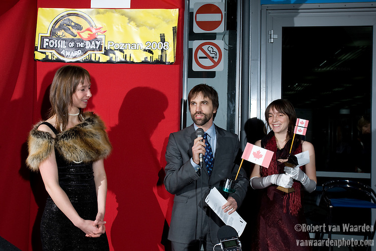 Steven Guilbeault (centre) from Equiterre, expresses his displeaure with the four fossils that Canada was awarded during the fourth day of UN Climate Change Negotiations. The Fossil of the Day award is given to the country that obstructs the process of Climate Change negotiations everyday. Also pictured, Katherine Trajan (left) and Thea Whitman (right) UNFCCC COP 14 (©Robert vanWaarden ALL RIGHTS RESERVED)