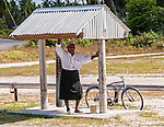 An elder awaits Sunday church service in the shade on the remote island of Kiritimati, Kiribati.