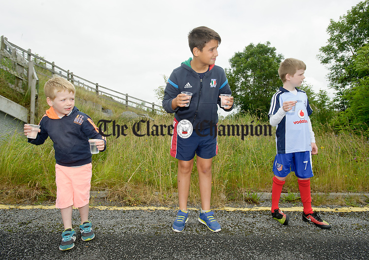Luka Prendergast, Nicolo Vinciguerrra and Calum Prendergast handing out water at the half way mark during the Martin Egan 10k road race in Shanaglish. Photograph by John Kelly.