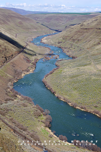 The lower Deschutes Canyon with the BNSF rail line, Deschutes River Trail, powerlines, and wheat fields.  Wind turbines along the Columbia River are visible in the distance.