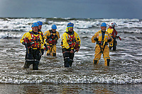 Pictured: RNLI crew in the sea. Tuesday 26 December 2017<br /> Re: Hundreds took part in this year's Boxing Day Walrus Dip which see people in fancy dress taking to the sea at Cefn Sidan beach in Pembrey Country Park, west Wales, UK.