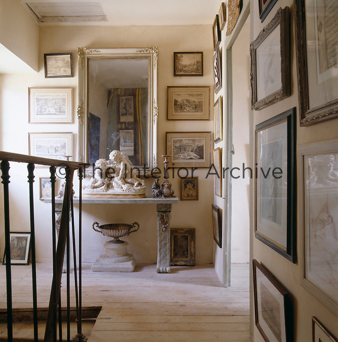 The walls of this corridor are lined from floor to ceiling with framed prints and engravings