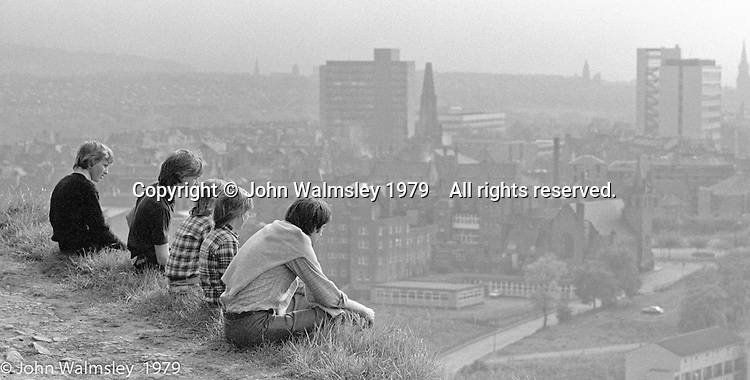 """Lads looking at a magnificent view of Edinburgh from """"Arthur's Seat"""", a steep granite hill, Edinburgh, Scotland, 1979.  John Walmsley was Photographer in Residence at the Education Centre for three weeks in 1979.  The Education Centre was, at the time, Scotland's largest purpose built community High School open all day every day for all ages from primary to adults.  The town of Wester Hailes, a few miles to the south west of Edinburgh, was built in the early 1970s mostly of blocks of flats and high rises."""