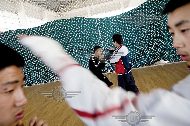 """Students training in a boxing class at the Qingdao City Sports School, one of the country's top breeding grounds for Olympic athletes. Principal Qiao Xiangdong credits the Beijing 2008 Olympic Games for spurring the local government to build a USD 42 million new campus for the academy's 600 students. """"Before, some parents were worried about sending their kids to sports schools because they thought their children would have to eat too much bitterness,"""" Qiao says, using the Chinese term for enduring hardship. """"But the Olympic Games have made people willing to contribute to the nation's glory."""""""