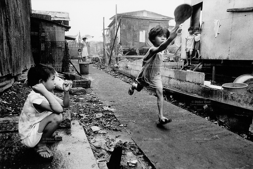 Philippines. Luzon Region. Manila. Tondo area. Smokey mountain is a rubbish dump. Life on a garbage heap. Group of children play on a path among wood huts.  © 1992 Didier Ruef .
