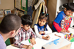 Education preschool 3-4 year olds young male teacher interacting with girl several students including boys drawing task observational drawing