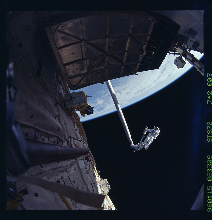 John Angerson. STS-72 Book.<br /> Public Domain Image.<br /> NASA images Courtesy National Archives - Record Group number: 255-STS-STS072<br /> Description: STS-72 Extravehicular Mobility Unit (EMU) suited Mission Specialist Dan Barry (EV2) conducts Portable Work Platform (PWP) evaluations high above the payload bay on the remote manipulator system (RMS) arm. These views were taken with a 70mm Hasselblad camera with a 35mm lens to create the fisheye effect.<br /> <br /> Subject Terms: STS-72, ENDEAVOUR (ORBITER), ASTRONAUTS, PAYLOAD BAY, EXTRAVEHICULAR ACTIVITY, EXTRAVEHICULAR MOBILITY UNITS, REMOTE MANIPULATOR SYSTEM<br /> <br /> Date Taken: 1/15/1996<br /> <br /> Categories: EVA<br /> <br /> Interior_Exterior: Exterior<br /> <br /> Ground_Orbit: On-orbit<br /> <br /> Original: Film - 70MM CT<br /> <br /> Preservation File Format: TIFF<br /> <br /> feat: NON-EARTHOBS<br /> <br /> nlat: 11.9<br /> <br /> nlon: -19.9<br /> <br /> azi: 114<br /> <br /> alt: 167<br /> <br /> elev: 10