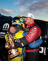 Nov 1, 2020; Las Vegas, Nevada, USA; NHRA funny car driver Matt Hagan (right) embraces teammate Ron Capps after winning the NHRA Finals at The Strip at Las Vegas Motor Speedway. Mandatory Credit: Mark J. Rebilas-USA TODAY Sports