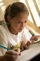 twelve year old girl doing her homework in her bedroom
