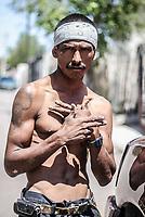Un pandillero sin camisa y con pañuelo en la cabeza hace una señales con sun manos para marcar territorio