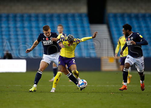 31st October 2020; The Den, Bermondsey, London, England; English Championship Football, Millwall Football Club versus Huddersfield Town; Shaun Hutchinson of Millwall challenges Juniho Bacuna of Huddersfield Town with James Brown of Millwall covering