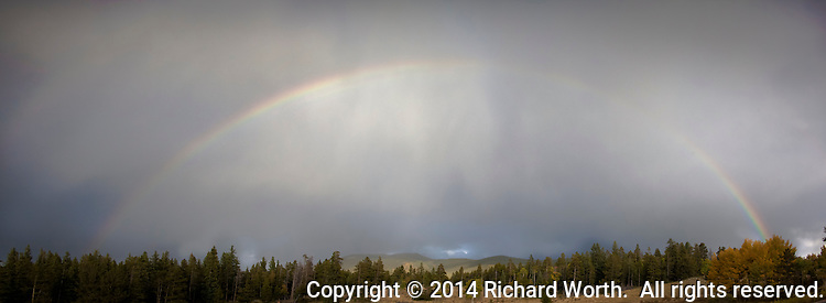 """In the midst of the Rocky Mountains a rainbrow stretches and teases, """"Come find the pot of gold."""""""