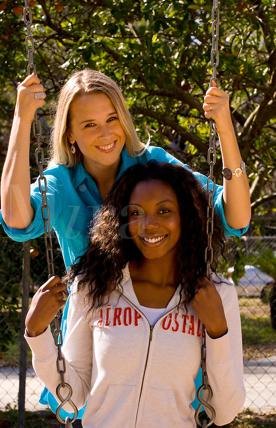Girlfriends on a swing outdoor in sunshine, mixed ethnic, white and black African American