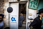 A Palestinian woman sits at her door way that has a graffiti of the star of David on it and looks at Jewish settlers celebrating the Purim holiday in a parade at the West Bank city of Hebron Sunday March 12 2017. Palestinians can't walk the street during the parade, Purim is a Jewish holiday that commemorates the saving of the Jewish people in ancient Persia , the story is recorded in the Biblical Book of Esther. Photo by Eyal Warshavsky