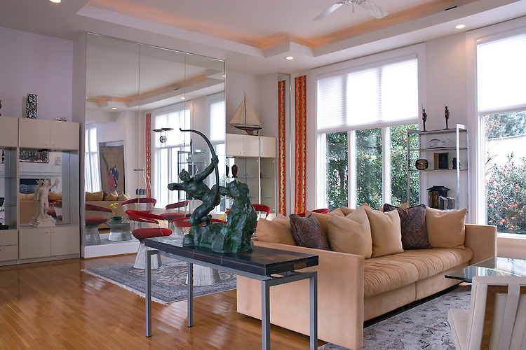 A modern designe living room with an Asian influence, featuring high ceilings, splashes of red color, and classic sculpture.