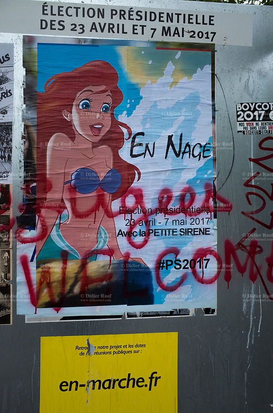 """France. Ile de France. Paris. Political opponents have glued a Little Mermaid poster on an official campaign poster  of French presidential election candidate Emmanuel Macron for the centrist party """"En Marche"""". A graffiti with handwritten words says """" Refugees welcome"""". The Little Mermaid is a 1989 American animated musical fantasy film produced by Walt Disney Feature Animation and released by Walt Disney Pictures. 22.04.17 © 2017 Didier Ruef"""
