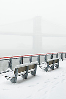Brooklyn Bridge and East River Viewed from East River Esplanade During a Snowstorm....Lower Manhattan, New York City, New York State, USA