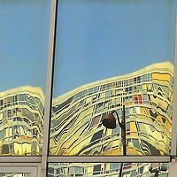 On a part of a mirror glass window, the twisted and colorful reflected image of a modern building (Paris, 2007).<br /> <br /> Su una parte di una finestra di vetro a specchio, l'immagine riflessa, colorata e distorta, di un edificio moderno (Parigi, 2007).