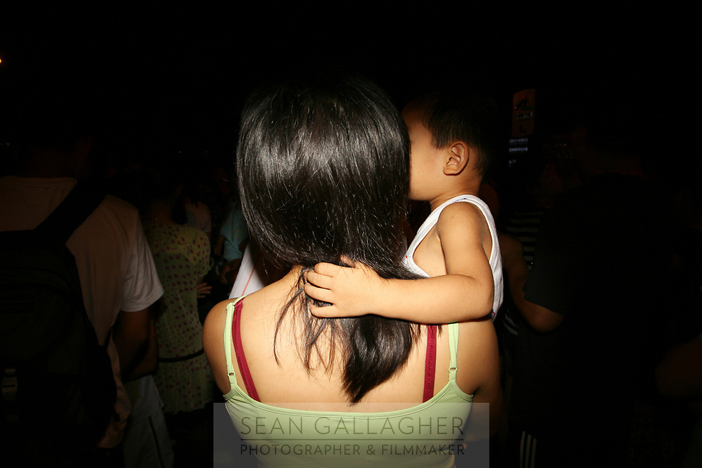 CHINA. Beijing. A mother carries her child in the Olympic village whilst watching rehearsals for the Beijing Olympic games. 2008