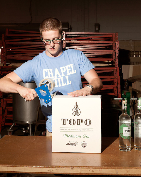 June 18, 2013. Chapel Hill, North Carolina<br />  Corey Bobeck, an employee of Top of the Hill Brewery, boxes bottles of TOPO Gin for shipping.<br />  TOPO, Top of the Hill Distillery, the brainchild of owner Scott Maitland and Spirit Guide Esteban McMahan, is located in the old N&O Building on Franklin Street. Making gin, vodka and American whiskey from locally sourced wheat, they are one of the few distilleries bringing  organic liquor to ABC shelves around the state.