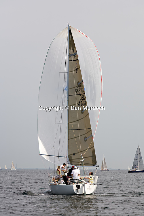 sloop sailing downwind with white spinnaker