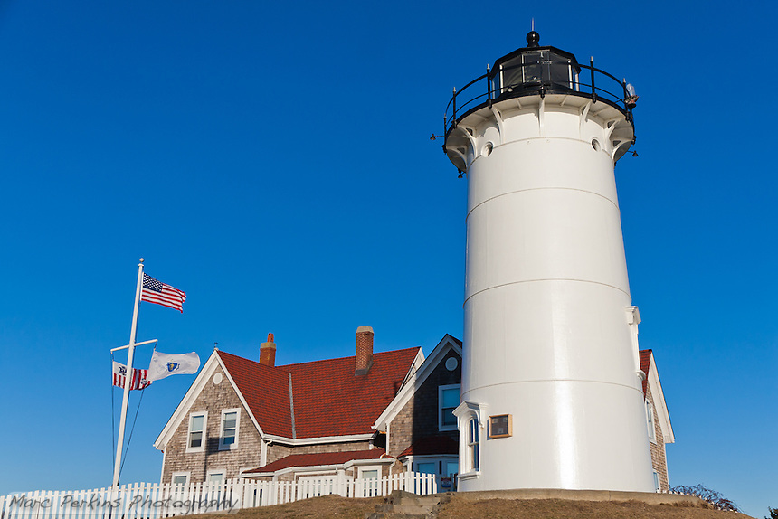 """Nobska Lighthouse in Woods Hole, MA on Cape Cod.  The red-roofed keeper's house and white and black lighthouse are both visible, as the wind blows the flags in front of a clear blue sky. I love how the lighthouse feels like it standing proud; a little bit of Americana.  This image is cropped to be printed at 12x18""""."""