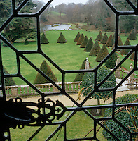 A view from a leaded window over the manicured gardens with conical topiary lining the lawn
