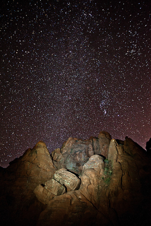 Stars rise above illuminated rock formation in the Valley of Fire State Park, Nevada, USA