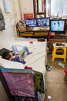 Zhenyuan, Guizhou, China.  Young Boy Watching Television in his Room, with Remote.