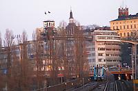 Blue train passing the bridge at Slussen with Katarinahissen The Katarina Elevator with the Gondolen restaurant in the background. The Stockholm subway. Stockholm. Sweden, Europe.